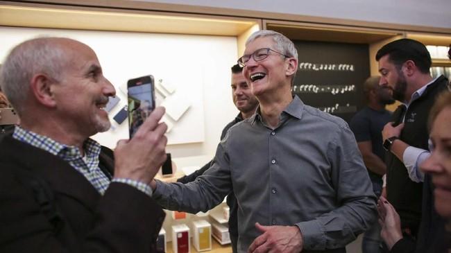CEO Apple Tim Cook ber-selfie ria dengan para karyawan serta meladeni permintaan berfoto dengan konsumen dalampembukaan penjualan iPhone 11 itu. (Photo by Kena Betancur / AFP)