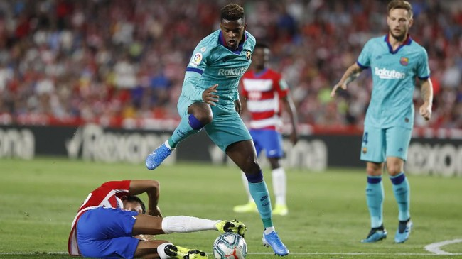 Bek kanan Barcelona, Nelson Semedo, berduel dengan pemain Granada, Angel Montoro, pada pertandingan yang berujung dengan kekalahanBlaugrana di Stadion Los Carmenes. (AP Photo/Miguel Morenatti)