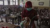 Petugas sekolah merapikan berkas di dalam ruangan kelas belajar mengajar yang kosong di SD N 15 Kota Pekanbaru, di Pekanbaru, Riau, Rabu (18/9/2019). ANTARA FOTO/Rony Muharrman