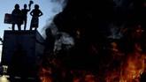 Sejumlah mahasiswa Universitas Hasanuddin (Unhas) Makassar membakar ban saat berunjuk rasa di depan kampus Unhas Makassar, Sulawesi Selatan, Senin (23/9). (ANTARA FOTO/Abriawan Abhe).