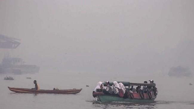 Sejumlah siswa menaiki kapal motor menembus kabut asap akibat kebakaran lahan di Sungai Ogan, Palembang, Sumatera Selatan, Senin (16/9). Kabut asap akibat karhutla telah mengganggu aktivitas masyarakat. ANTARA FOTO/Mushaful Imam