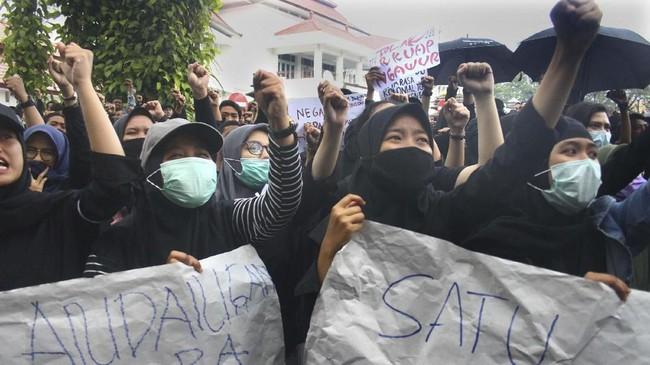 Mahasiswa membawa poster saat berunjuk rasa di depan Gedung DPRD, Malang, Jawa Timur, Senin (23/9). Unjuk rasa ribuan mahasiswa yang dilakukan secara bergelombang dari sejumlah perguruan tinggi tersebut menuntut pembatalan UU KPK. (ANTARA FOTO/Ari Bowo Sucipto/ama).