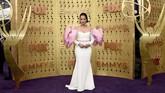 Dascha Polanco seperti tengah membawa beban berat di kedua lengannya. Gaun putih dan merah muda itu terlihat sangat aneh. (Photo by Jordan Strauss/Invision/AP)