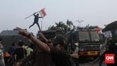 Mahasiswa melempari aparat keamanan dengan batu dan botol mineral untuk membalas tembakkan gas air mata yang dilepaskan aparat keamanan di depan gedung DPR.(CNN Indonesia/Bisma Septalisma)
