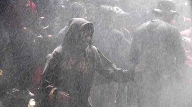Mahasiswa berlindung dari semprotan meriam air milik polisi saat terjadi bentrok dalam unjuk rasa Hari Tani Nasional di depan Gedung DPRD, Malang, Jawa Timur, Selasa (24/9). Akibat bentrokan tersebut sejumlah mahasiswa dan polisi terluka. (ANTARA FOTO/Ari Bowo Sucipto)