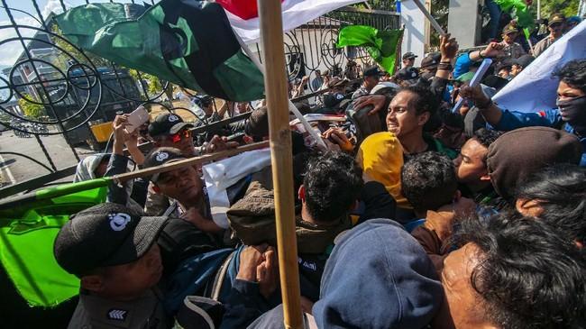 Mahasiswa terlibat aksi dorong-dorongan dengan aparat keamanan pada unjuk rasa menolak RUUKUHP di depan Kantor DPRD Sulawesi Tengah di Palu, Selasa (24/9). Unjuk rasa yang digelar Himpunan Mahasiswa Islam (HMI) Sulteng itu diakhiri dengan penandatanganan penolakan RUU KUHP oleh anggota DPRD Sulteng. (ANTARA FOTO/Basri Marzuki)