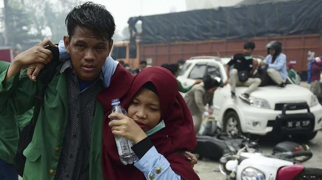 Mahasiswa yang tergabung dalam Aliansi Sumsel Melawan menyelamatkan diri saat terlibat bentrok dengan aparat keamanan saat melakukan aksi di luar gedung DPRD Sumatera Selatan, Palembang, Sumatera Selatan, Selasa (24/9). Aksi untuk menolak pengesahan RUU KUHP dan menolak UU KPK tersebut berakhir ricuh. (ANTARA FOTO/Mushaful Imam)