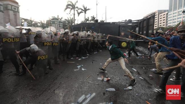 Sejumlah mahasiswa mencoba menaiki gerbang DPR untuk masuk ke dalam gedung. Mahasiswa juga mencorat-coret gedung. (CNN Indonesia/Bisma Septalisma).
