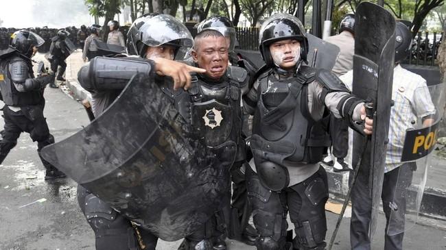 Seorang petugas kepolisian dibantu rekannya saat terkena lemparan batu di depan gedung DPRD Sumut, di Medan, Sumatera Utara, Selasa (24/9). Aksi yang diikuti mahasiswa dari berbagai kampus itu berakhir ricuh dan bentrok. (ANTARA FOTO/Septianda Perdana)