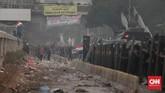 Mahasiswa membakar pembatas jalan saat kericuhan di depan gedung DPR. Aparat kemudian memadamkan api dan menembakan gas air mata ke arah mahasiswa. (CNN Indonesia/Bisma Septalisma).
