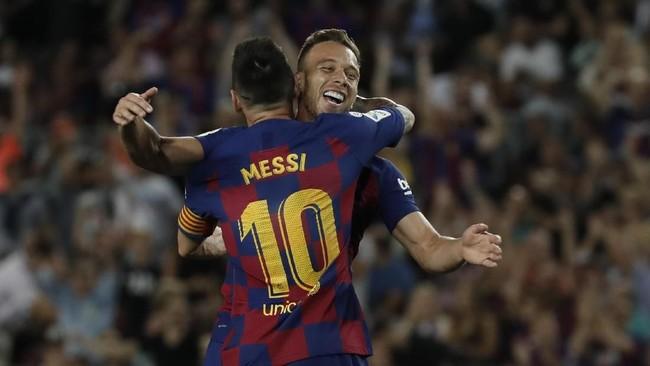 Barcelona kemudian menggandakan keunggulan pada menit ke-15 melalui gol Arthur Melo. Lionel Messi merayakan gol bersama Arthur. (AP Photo/Joan Monfort)