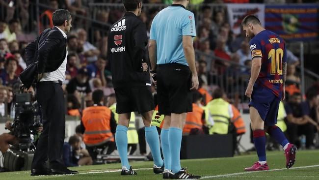 Lionel Messi berjalan ke pinggir lapangan untuk menerima perawatan tim medis dengan pelatih Barcelona Ernesto Valverde melihat ke arah La Pulga. (AP Photo/Joan Monfort)
