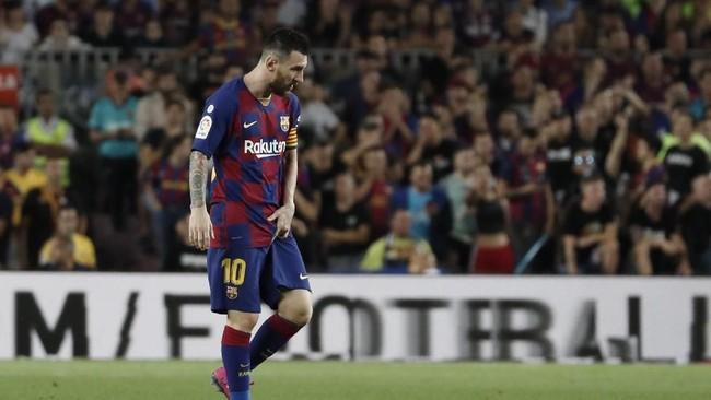 Lionel Messi berjalan ke dalam lapangan dengan masih mengeluh sakit pada bagian paha kiri. Messi tetap mampu melanjutkan pertandingan usai mendapat perawatan tim medis. (AP Photo/Joan Monfort)