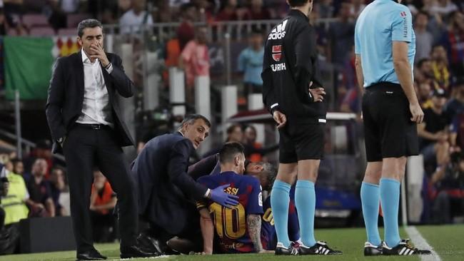 Lionel Messi mendapat perawatan tim medis di saat pelatih Barcelona Ernesto Valverde (kiri) mengamati pertandingan melawan Villarreal. (AP Photo/Joan Monfort)