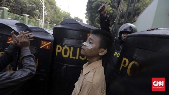 Aparat kepolisian mencoba mengadang massa pelajar yang mengendarai sepeda motor di Jalan Gatot Subroto di depan Mapolda Metro Jaya. Mereka pun digeledah, dan disuruh jalan jongkok ke markas polisi. (CNNIndonesia/Adhi Wicaksono)