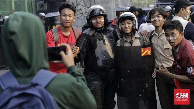 Saat melakukan pengamanan aksi massa pelajar sekolah menengah di belakang Gedung DPR, polisi mencoba ajakan persuasif lewat pengeras suara dengan mengingatkan hormat kepada yang lebih tua dan hindari provokasi. (CNN Indonesia/Adhi Wicaksono)