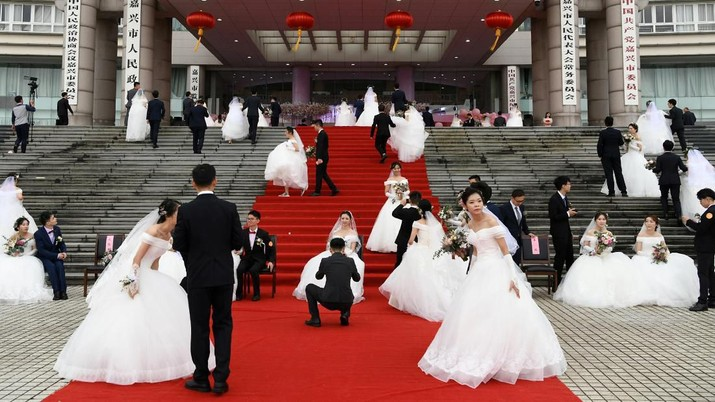 Couples attend a mass wedding at the city's municipal government building ahead of the 70th founding anniversary of People's Republic of China in Jiaxing, Zhejiang province, China September 22, 2019. REUTERS/Stringer ATTENTION EDITORS - THIS IMAGE WAS PROVIDED BY A THIRD PARTY. CHINA OUT.     TPX IMAGES OF THE DAY