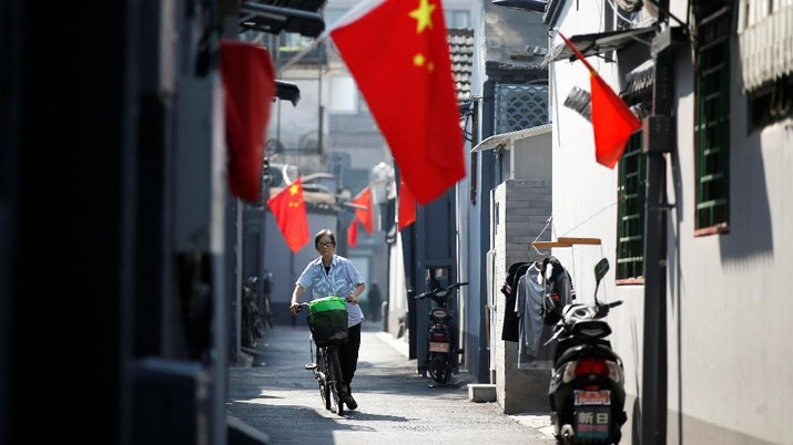 A resident cycles along a traditional alleyway, or hutong, with Chinese national flags to mark the 70th founding anniversary of People's Republic of China on October 1, in Beijing, China September 26, 2019. REUTERS/Jason Lee