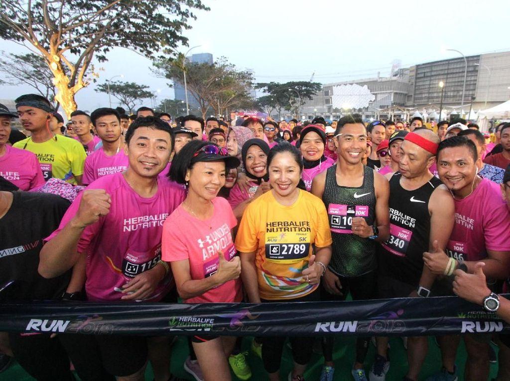Senior Director and General Manager Herbalife Nutrition Indonesia Andam Dewi (tiga kiri) bersama Triatlit Nasional Jauhari Johan (empat kanan) dan dan ribuan peserta lomba lari bersiap melakukan start pada lomba lari Herbalife Run 2019.