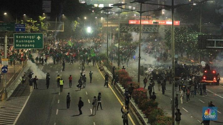 Aksi saling serang terjadi antara massa dan petugas kepolisian.