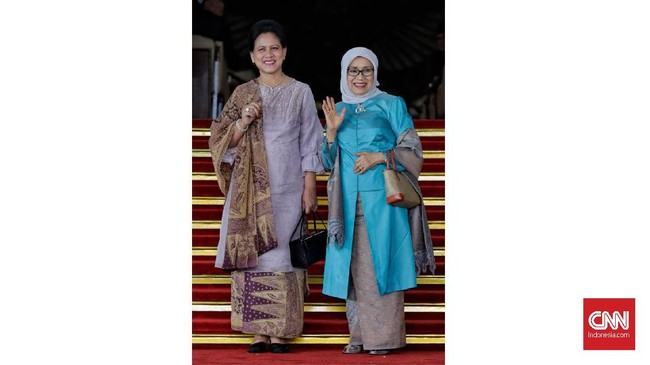 Ibu Negara Iriana Joko Widodo danMufidah Jusuf Kalla memakai baju kurung dengan warna ungu pucat dan biru terang. (CNN Indonesia/ Adhi Wicaksono)
