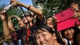 Sejumlah warga China di Beijing mengabadikan parade militer itu menggunakan gawai masing-masing. (Photo by HECTOR RETAMAL / AFP)