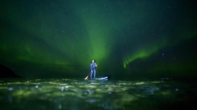 Surfer Indonesia, Edi Siswanto, sedang menikmati sensasi menaikiStand-Up Paddleboad (SUP)di bawah aurora saat mengunjungi Teluk Unstad.