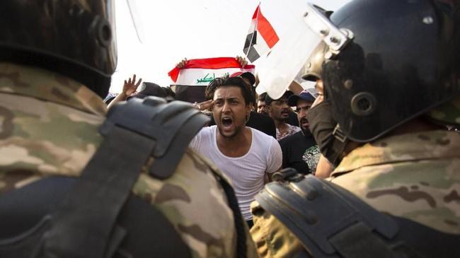 Sebagian besar demonstran membawa bendera Irak, sementara yang lain mengibarkan bendera bertuliskan nama Hussein, cucu Nabi Muhammad dan tokoh yang dihormati dalam Islam Syiah. (Photo by Hussein FALEH / AFP)