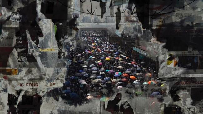 Aksi protes anti-pemerintah Hong Kong terlihat dari suatu kaca yang dipasang poster yang telah terkelupas. Sementara di Beijing, rakyat China sedang merayakan 70 tahun Republik Rakyat China. (AP Photo/Vincent Yu)