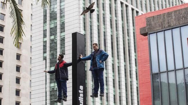 Henry Vargas (kiri) and Klauss Duraes terlihat melakukan trik levitasi menggunakan telapak tangan pada suatu papan penanda di Sao Paulo, Brasil. Ilusionis asal Brasil ini tampil empat jam dan memecahkan rekor sebelumnya selama tiga jam dan 20 menit. (AP Photo/Andre Penner)