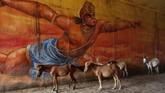 Di depan tembok yang dilukis gambar Dewa Hanoman, keledai-keledai berdiri di bawah jembatan overpass di Prayagraj, India. (AP Photo/Rajesh Kumar Singh)