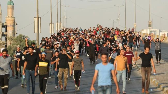 Ribuan pengunjuk rasa bentrok dengan polisi antihuru-hara di ibu kotaIrak dan di selatan negara tersebut, Kamis (3/10). Pada hari ketigademonstrasi itu, jumlah massa aksi yang tewas sebanyak 28 orang. (AP Photo/Hadi Mizban)