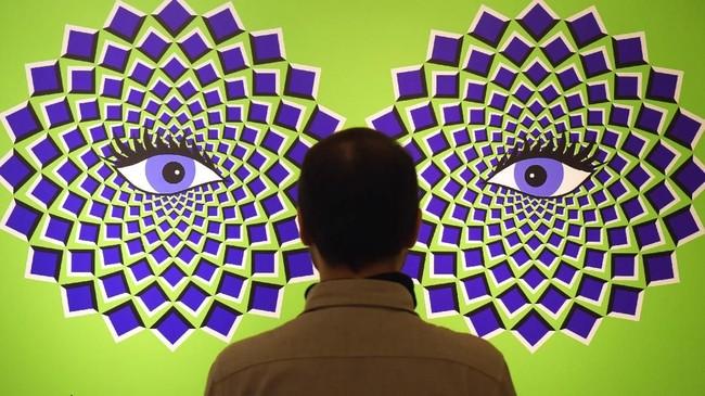 Seorang pria berdiri di depan suatu ilusi optik pada pameran interaktif