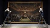 Para pegawai rumah lelang Sotheby melihat lukisan oleh seniman jalanan Banksy yang sedang dipajang di ruang lelang di London. Lukisan ini diperkirakan berharga US$1,8 juta-2,5 juta. (AP Photo/Kirsty Wigglesworth)