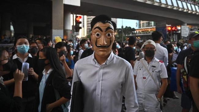 Topeng wajah seorang pria bermata bundar serta kumis ala Salvador Dali ini menjadi salah satu yang hadir meramaikan aksi unjuk rasa. (Philip FONG / AFP)
