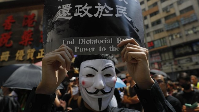 Beberapa pihak mengklaim bahwa aturan ini dirancang menyusul tuntutan masyarakat yang khawatir karena selama ini perusuh demonstrasi sebagian besar adalah pendemo yang mengenakan wajah. (AP Photo/Vincent Thian)