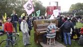 Unjuk rasa menentang perubahan iklim dilakukan dengan berbagai cara. Salah satunya dengan sambil bermain piano seperti yang dilakukan di Parc de la Vilette ,Paris, Prancis. (Photo by JACQUES DEMARTHON / AFP)