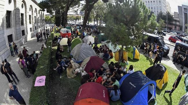 Aktivis perubahan iklim Spanyol melakukan aksi unjuk rasa dengan menggelar tenda di depan Kementerian Perubahan Ekologi di Madrid. (Photo by OSCAR DEL POZO / AFP)
