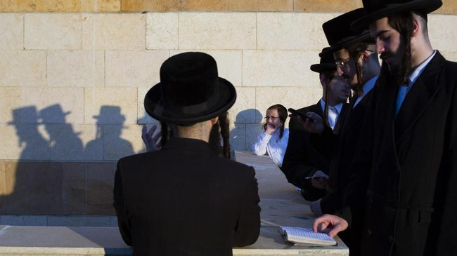 Dalam upacara Tashlich, orang-orang Yahudi pergi ke genangan air besar dan secara simbolis 'membuang' dosa-dosa dengan melemparkan sepotong roti atau makanan serupa ke dalam air. (AP Photo/Oded Balilty)