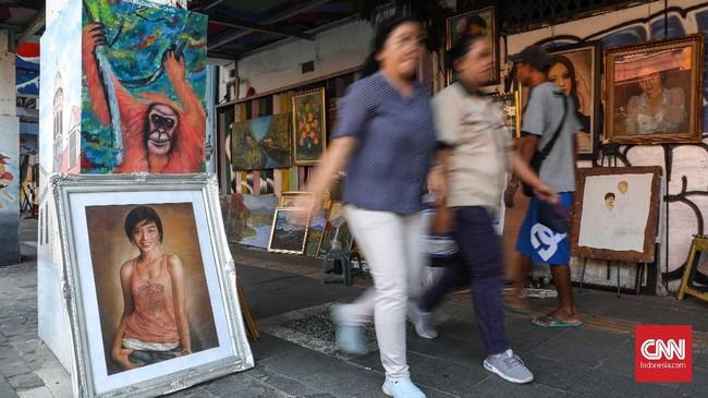 Para pelukis itu memanfaatkan lokasi di depan ruko-ruko sepanjang jalan. Mereka pun lebih leluasa jika ruko tersebut melewati jam operasional dan tutup. (CNNIndonesia/Safir Makki)
