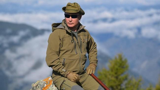 Putin memilih menyalurkan hobi bertualang dengan mendaki pegunungan Siberia. Dia terlihat tengah rehat sejenak di tengah kegiatan mendaki. (Alexei Druzhinin, Sputnik, Kremlin Pool Photo via AP)