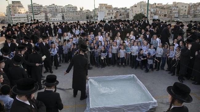 Orang-orang Yahudi Ultra-Ortodoks mengelilingi kolam plastik berisi air. Mereka tengah serta dalam upacara Tashlich. (AP Photo/Oded Balilty)