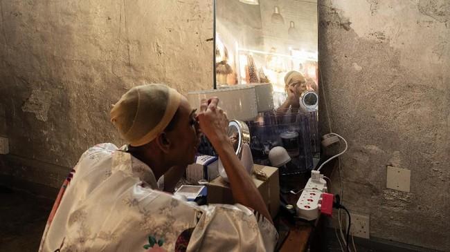 Seorang penampil dalam festivalDiabolique sedang berdandan di ruang ganti.(AFP/Luca Sola)