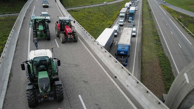 Petani di seantero Prancis berunjuk rasa dengan memarkir traktor mereka di jalan bebas hambatan utama di dekat Mulhouse. (Photo by SEBASTIEN BOZON / AFP)