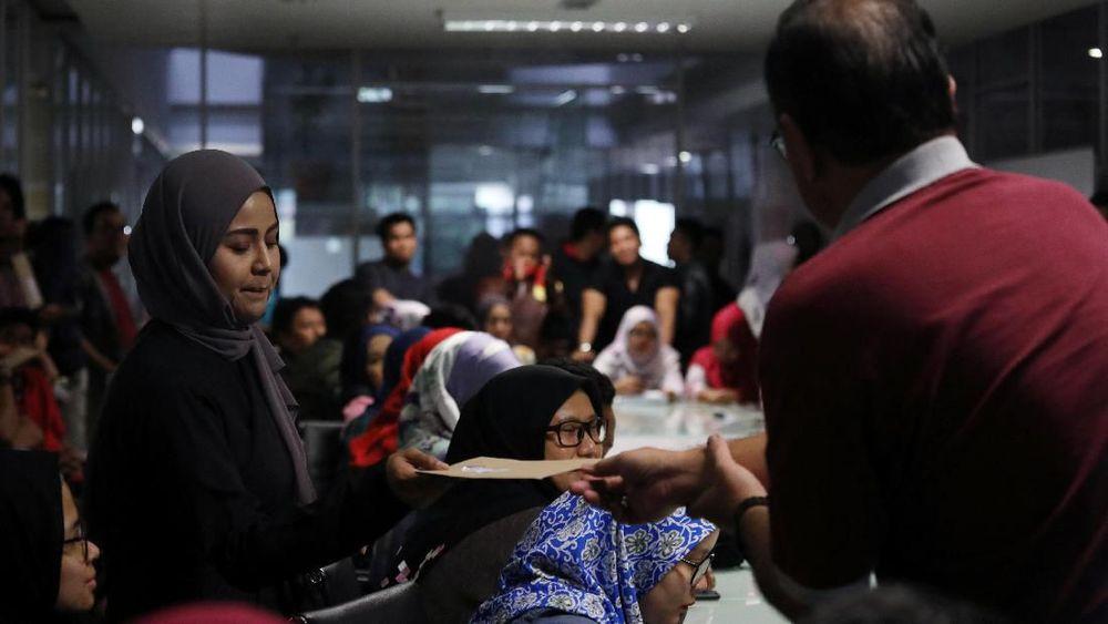 Karyawan menerima surat pemberhentian dari manajemen Utusan Malaysia di kantor pusat perusahaan di Kuala Lumpur.Sebuah koran asal Malaysia berusia 80 tahun tutup. Koran bernama Utusan Malaysia ini sudah bertahun-tahun mengalami masalah keuangan. REUTERS/Lim Huey Teng