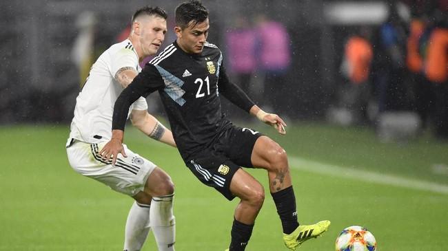 Penyerang timnas Argentina Paulo Dybala mendapat pengawalan ketat dari bek tengah timnas Jerman Niklas Sule dalam laga uji coba yang berakhir imbang 2-2. (AP Photo/Martin Meissner)