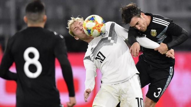 Gelandang timnas Jerman Julian Brandt berduel dengan pemain belakang Nicolas Tagliafico dalam pertandingan yang berakhir tanpa pemenang dengan skor 2-2. (AP Photo/Martin Meissner)