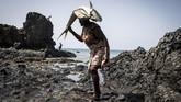 Seorang perempuan membawa ikan di kepalanya setelah dibersihkan di sebuah kampung nelayan di Porto Mosquito, Cape Verde. (AFP/John Wessels)