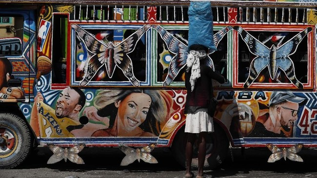 Seorang perempuan menjual tas berisi air kepada para penumpang yang menunggu di dalam mini bus, saat protes anti-pemerintah di Port-au-Prince, Haiti. (AP/Rebecca Blackwell)