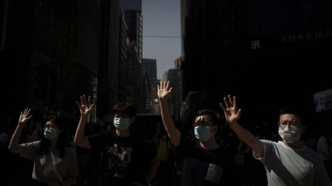 Para demonstrasn pro-demokrasi berkumpul di pusat kota sebelum rencana pemerintah untuk melarang orang memakai masker dalam demonstrasi panjang di Hong Kong. (AP/Felipe Dana)